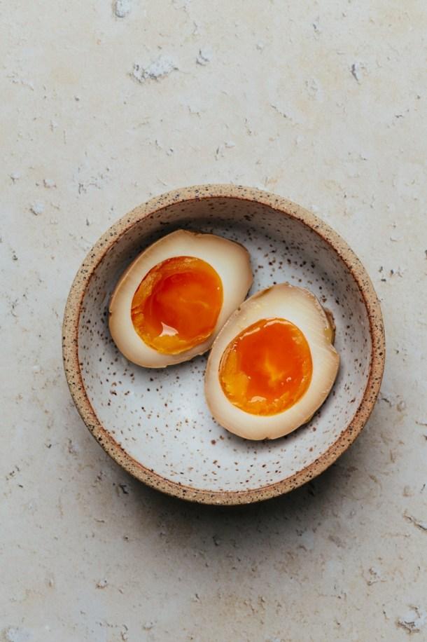 a bowl containing two soy sauce ramen egg halves