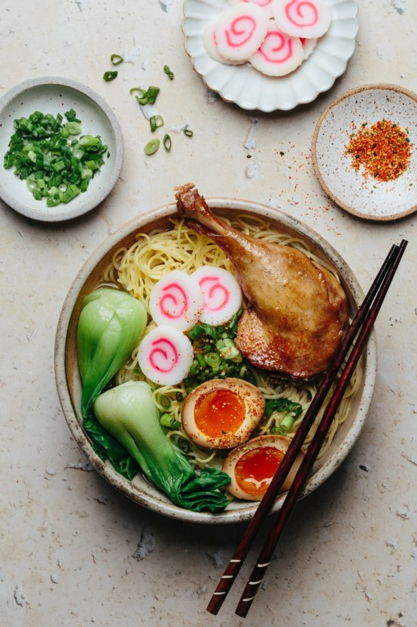 a ramen bowl with a pair of chopsticks resting on top next to a bowl of fish cake, a bowl of scallion, and a bowl of togarashi