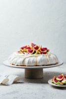 Earl Grey pavlova on cake stand next to a plate of fresh figs and kitchen linen