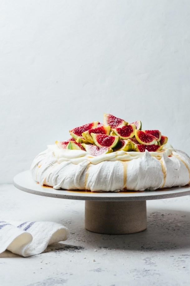 Earl Grey pavlova on cake stand next to a kitchen linen