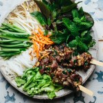 a bowl filled with grilled pork, vermicelli noodles, Vietnamese herbs, cucumber, bean sprouts, pickled vegetables, roasted peanuts, and dipping sauce