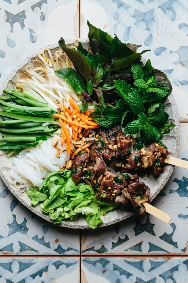 a bowl containing grilled pork skewers, vermicelli noodles, cucumber, bean sprouts, Vietnamese herbs, lettuce, pickled vegetables, roasted peanuts and dipping sauce