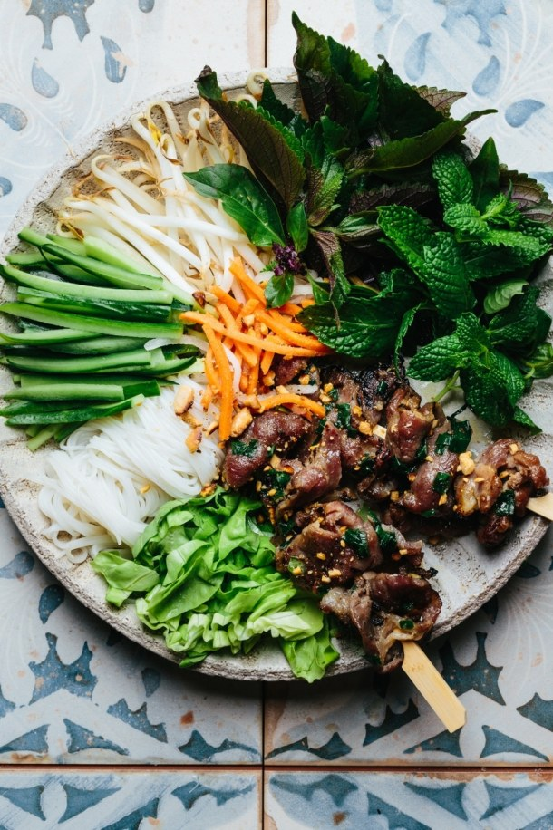 a close up of a bowl containing grilled pork skewers, vermicelli noodles, cucumber, bean sprouts, Vietnamese herbs, lettuce, pickled vegetables, roasted peanuts and dipping sauce