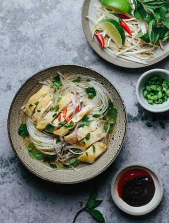 a bowl of pho ga next to a bowl of condiment, a bowl of scallion, a plate containing Thai basil, Vietnamese mint, bean sprouts, lime wedges, and bird's eye chilis