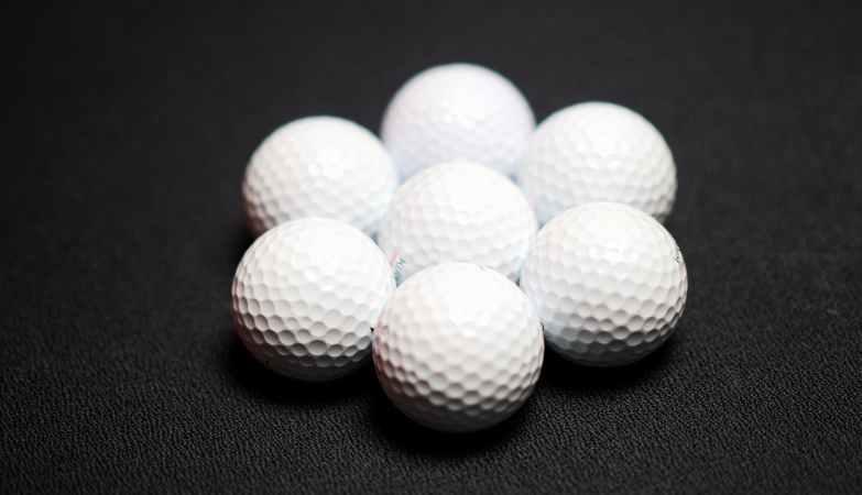 set of golf balls on black background