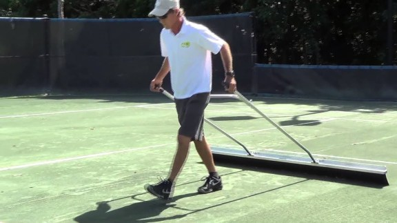 tennis pro sweeping courts