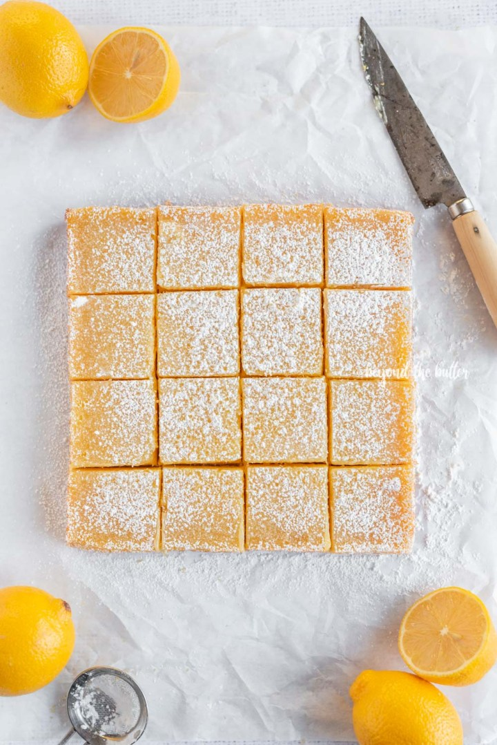 Overhead image of just sliced lemon bars with knife and lemons | All Images © Beyond the Butter, LLC