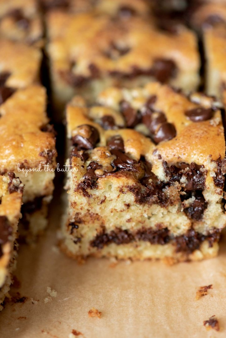 Chocolate chip sour cream coffee cake on brown parchment paper | © Beyond the Butter®