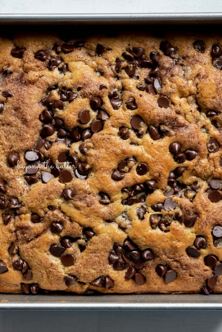 Close up of chocolate chip sour cream coffee cake in 8 inch baking pan | © Beyond the Butter®