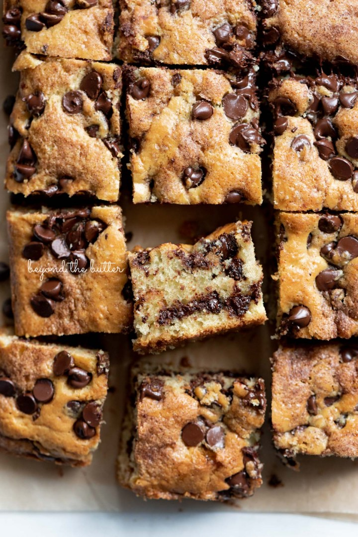 Cut squares of chocolate chip sour cream coffee cake on brown parchment paper with randomly placed chocolate chips | © Beyond the Butter®