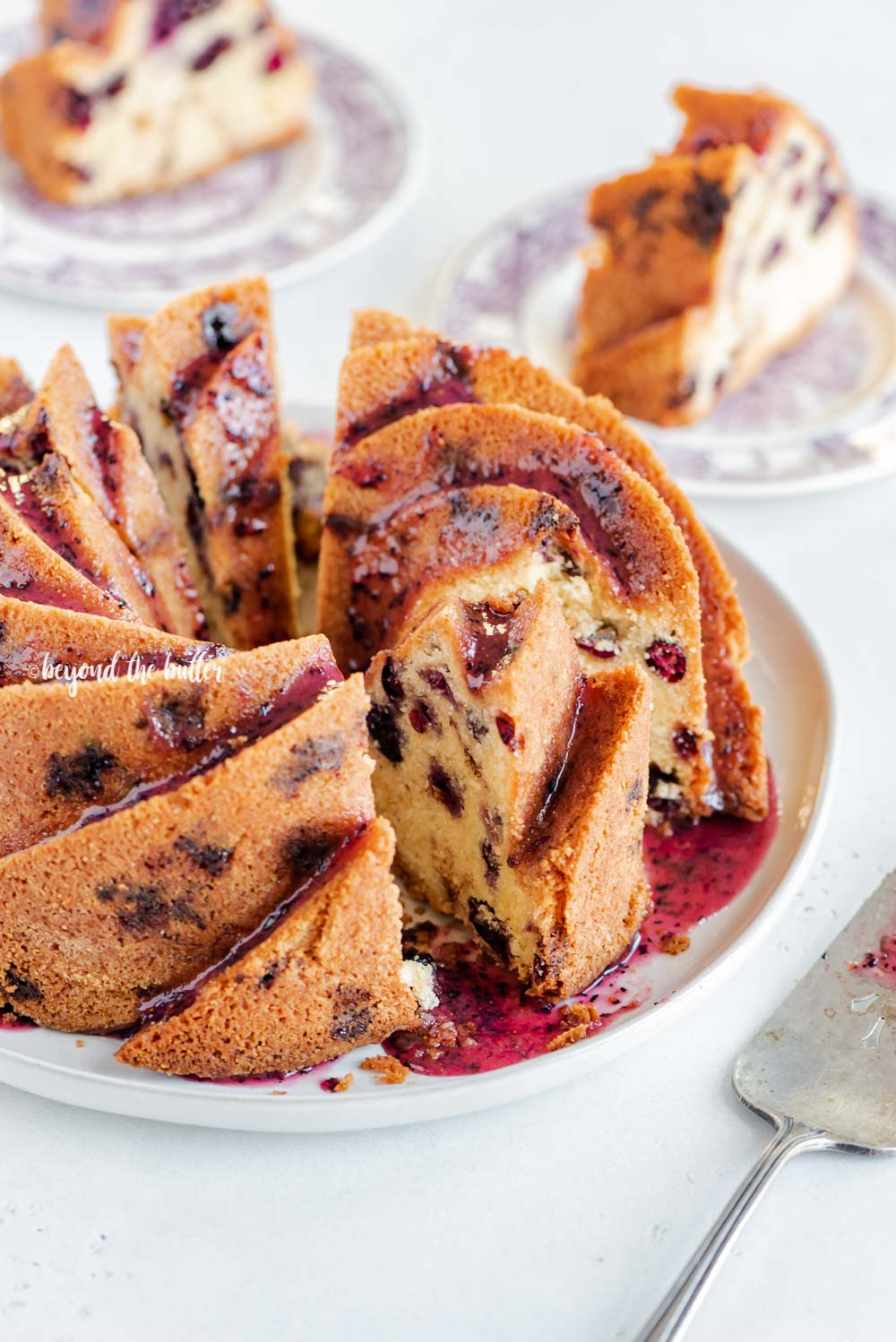 Angled image of sliced blueberry bundt cake with blueberry glaze drizzled over the top | All Images © Beyond the Butter, LLC