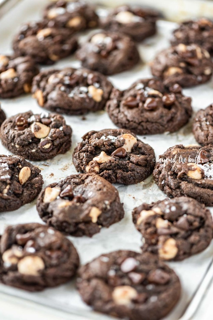 Angled image of just baked double chocolate salted caramel cookies on a baking sheet   All Images © Beyond the Butter™