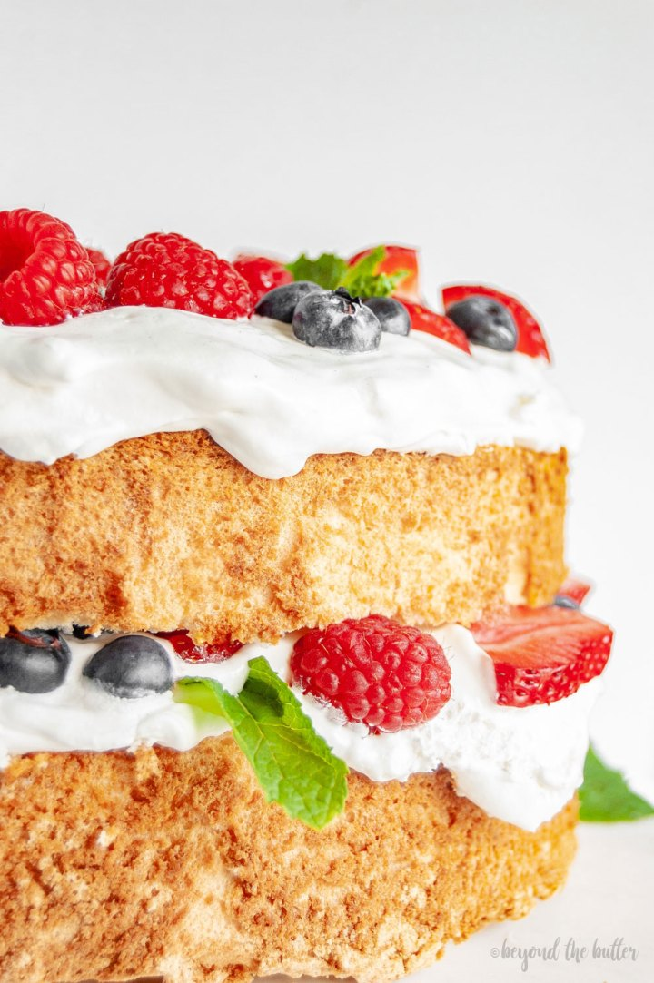 Angel Food Cake with Berries | Close up image of Angel Food Cake on a cake stand | Image and Copyright Policy: © Beyond the Butter, LLC