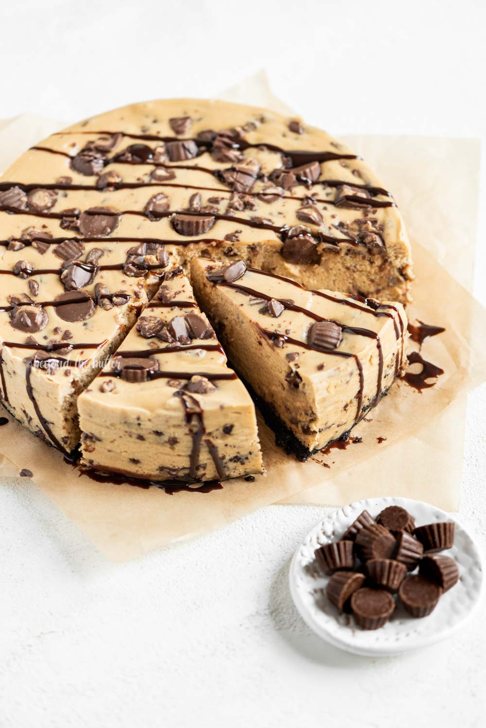 Angled image of sliced Reese's Peanut Butter Cup Cheesecake drizzled with chocolate | All Images © Beyond the Butter, LLC