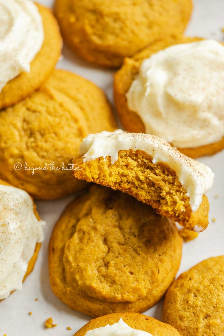 Plain and frosted pumpkin cinnamon cookies with one angled up and half eaten on a white background | All Images © Beyond the Butter™