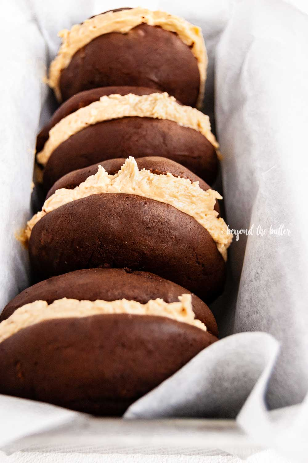 Angled image of chocolate peanut butter whoopie pies stacked in a parchment lined baking pan | All images © Beyond the Butter™