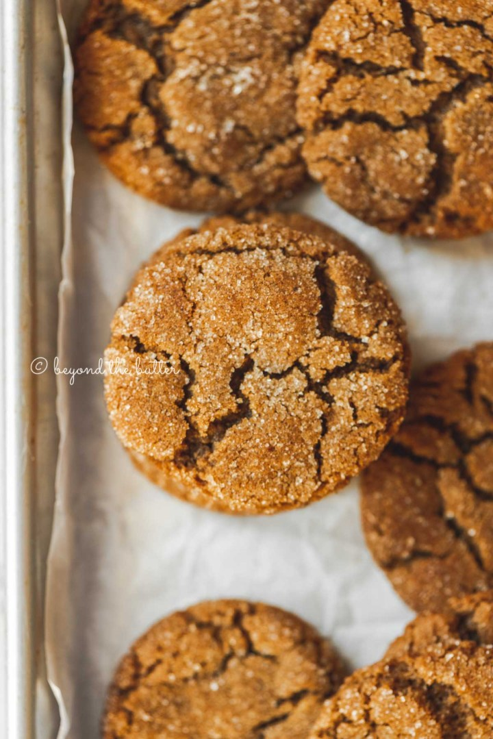 Overhead image of soft molasses sugar cookies on a parchment paper lined baking sheet | All Images © Beyond the Butter™