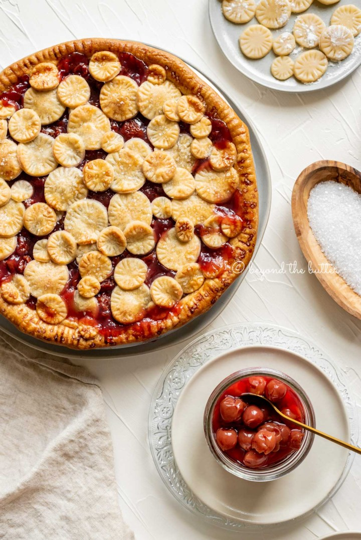 Overhead image of cherry pie surrounded by plates, jar of cherries, sprakling sugar, and pie crust toppers | All Images © Beyond the Butter™