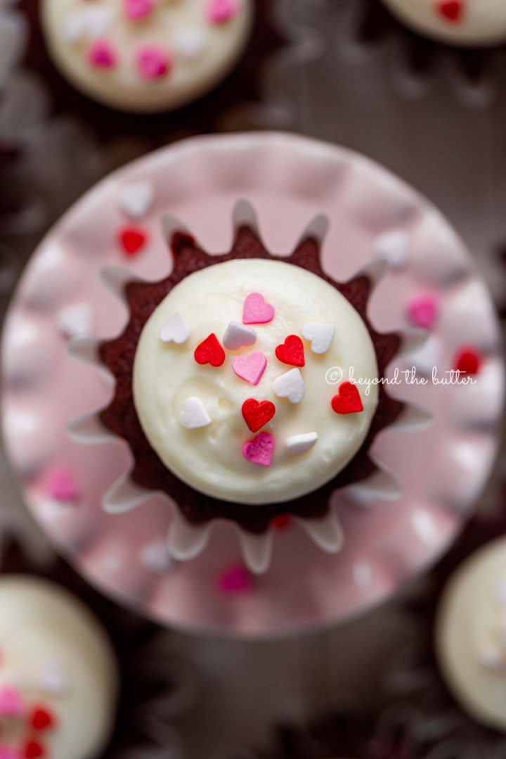 Homemade red velvet cupcakes with cream cheese frosting topped with heart sprinkles on a a small pink cupcake stand | All images © Beyond the Butter®