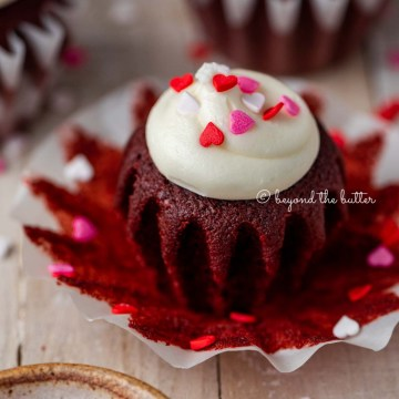 Opened red velvet cupcake with cream cheese frosting topped with heart sprinkles on a light wood background | All images © Beyond the Butter®