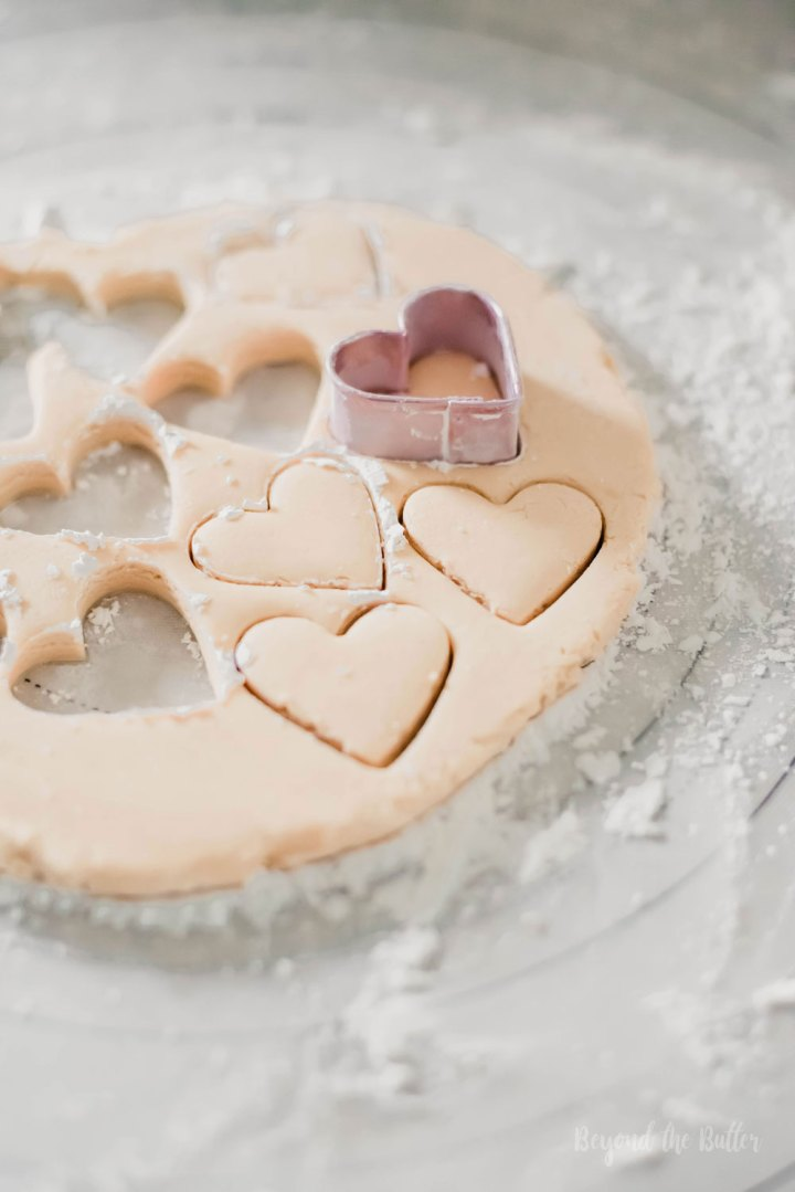 Chocolate Covered Peanut Butter Hearts | Cutting out peanut butter hearts with a small heart shaped cookie cutter | Image and Copyright Policy: Beyond the Butter, LLC