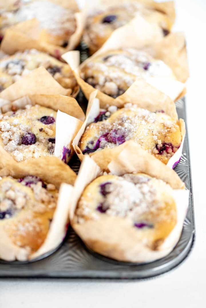 Angled image of bakery style lemon blueberry streusel muffins in a muffin tin | All Images © Beyond the Butter™