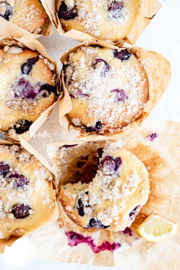 Overhead image of bakery style lemon blueberry streusel muffins with one half eaten | All Images © Beyond the Butter™