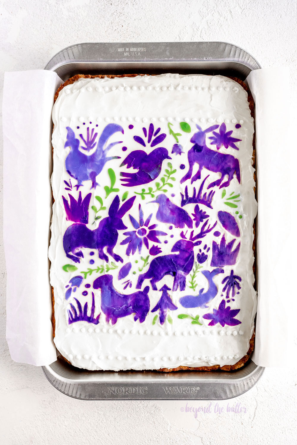 Hummingbird Sheet Cake with White Chocolate Cream Cheese Frosting | Overhead photo of Hummingbird Sheet Cake that's topped with a white chocolate frosting, and stenciled using purple and green frosting | Image and Copyright Policy: © Beyond the Butter, LLC.