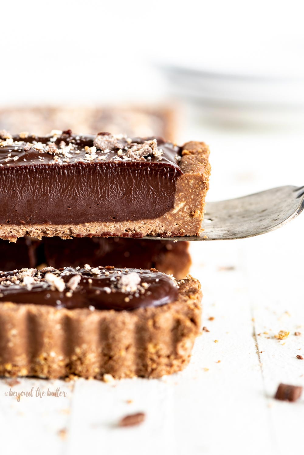 No-bake Dark Chocolate Tart | Close-up photo of a slice of no-bake dark chocolate tart being lifted up with a serving utensil | Image and Copyright Policy: © Beyond the Butter, LLC