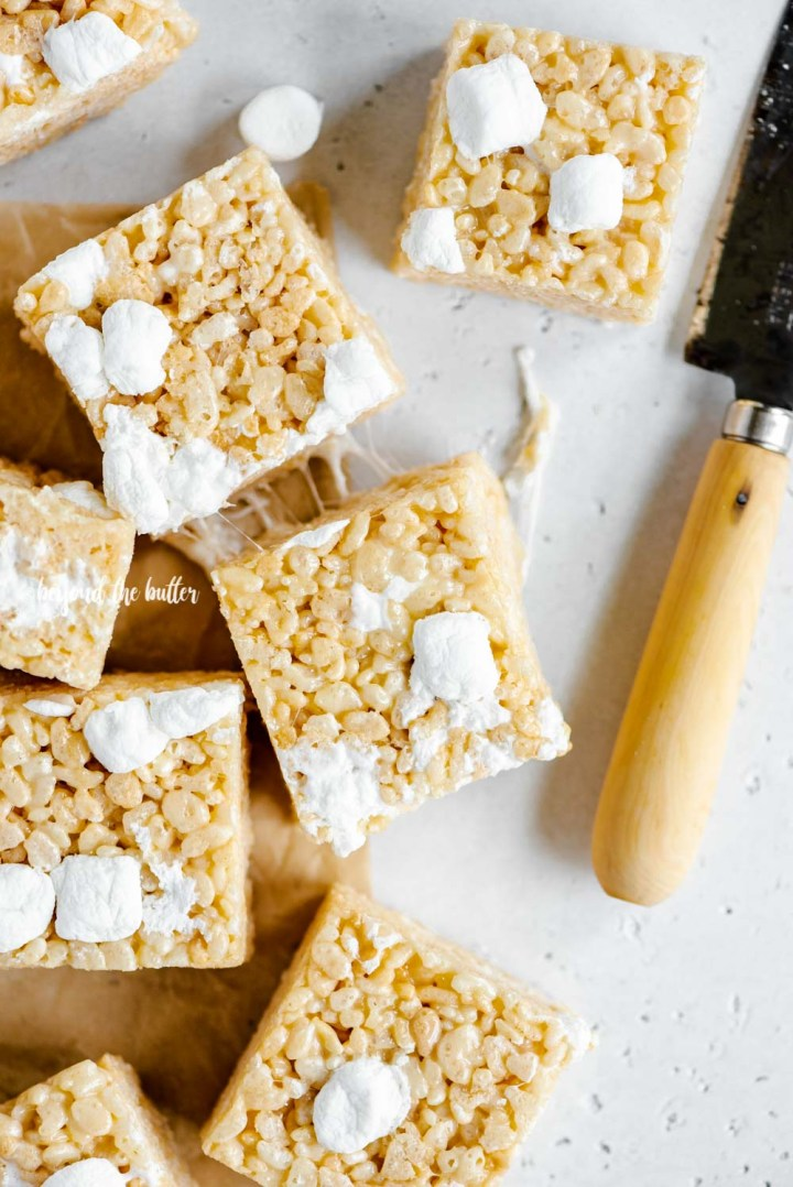 Overhead image of just cut rice krispie treats on parchment paper with a knife placed to the right | All Images © Beyond the Butter™
