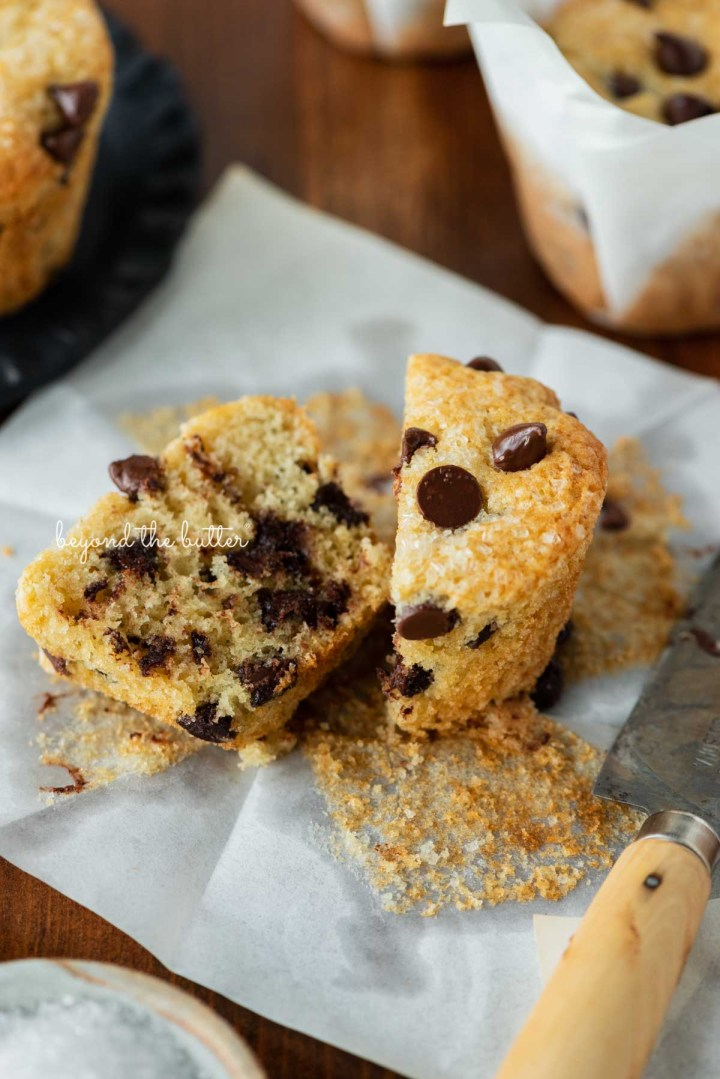 Bakery style chocolate chip muffin sliced in half laying on the tulip style liner   © Beyond the Butter®