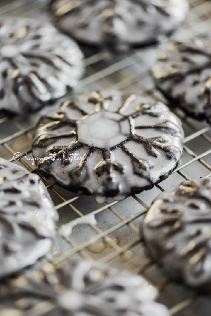 Angled closeup image of homemade oreo snowflake cookies on a wire cooling rack | All Images © Beyond the Butter®