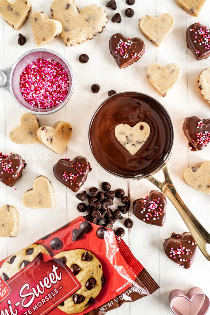 Dipping chocolate chip cookie dough hearts in melted chocolate | All Images © Beyond the Butter, LLC