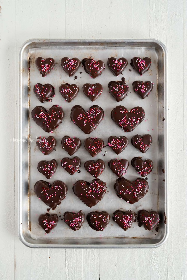 Overhead image of chocolate covered cookie dough hearts with sprinkles   All Images © Beyond the Butter, LLC