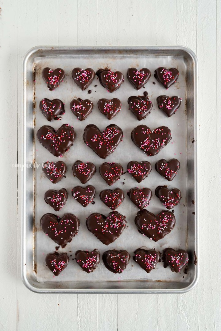 Overhead image of chocolate covered cookie dough hearts with sprinkles | All Images © Beyond the Butter, LLC