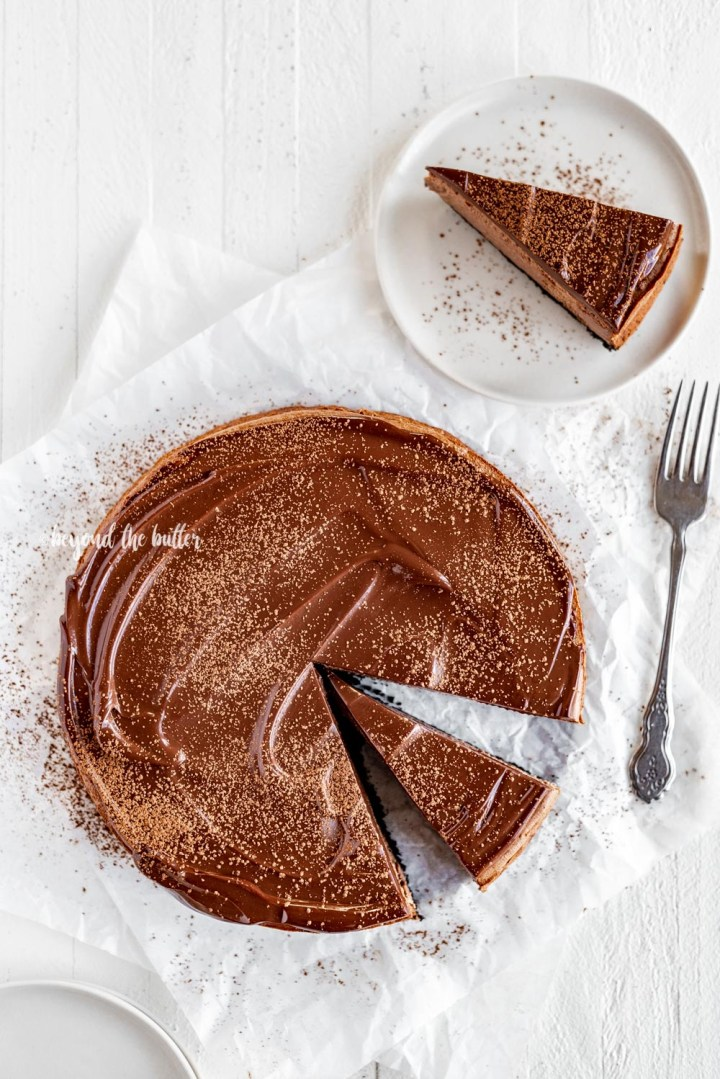Overhead image of Triple Chocolate Mocha Cheesecake dusted with cocoa and a slice removed set on a dessert plate with a fork | All Images © Beyond the Butter, LLC