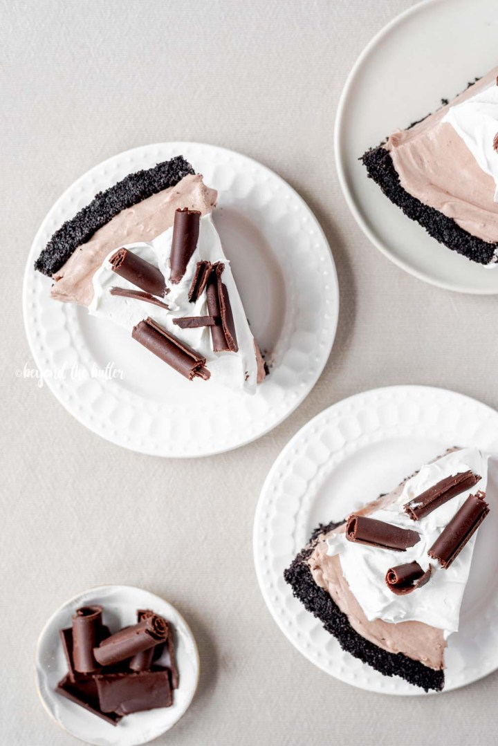 Slices of no-bake chocolate cream pie with chocolate wafer crust on dessert plates | All Images © Beyond the Butter™