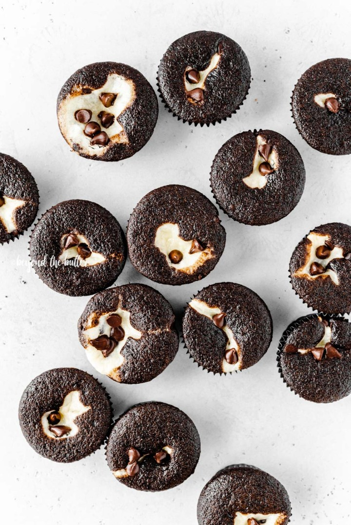 Overhead image of black bottom cupcakes randomly placed on gray background | All Images © Beyond the Butter™