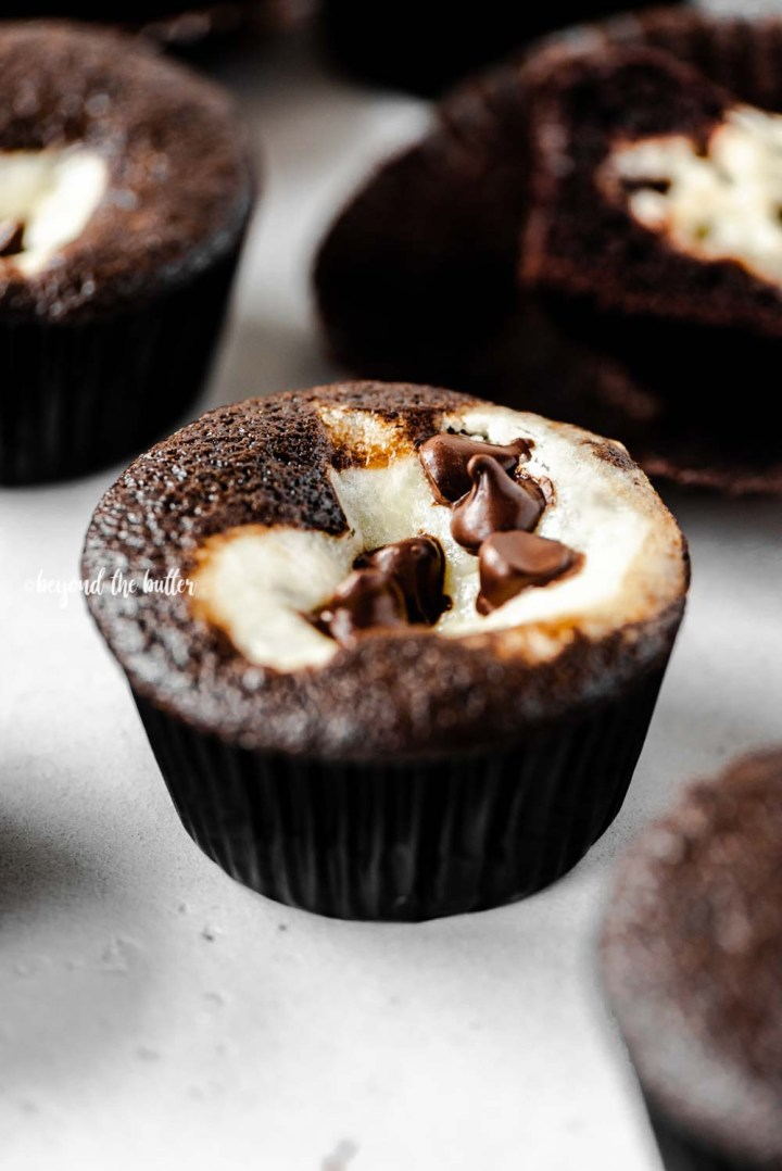 Close up angled image of black bottom cupcakes randomly placed on gray background | All Images © Beyond the Butter™