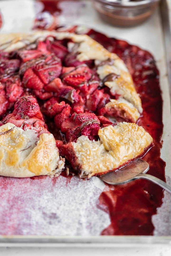 Angled image of a Berry Nutella Galette on a baking sheet with Nutella drizzled over the top and 2 slices cut | All Images © Beyond the Butter™
