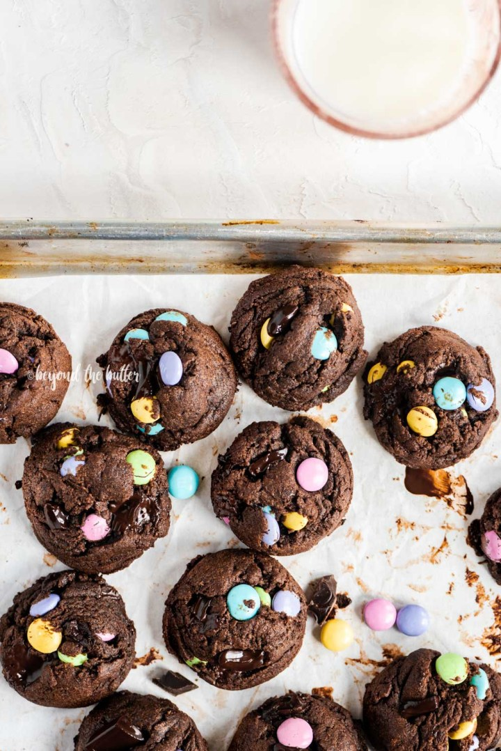Overhead image of just baked double chocolate chunk m&m cookies on a parchment lined baking sheet and a glass of milk above it | All Images © Beyond the Butter™