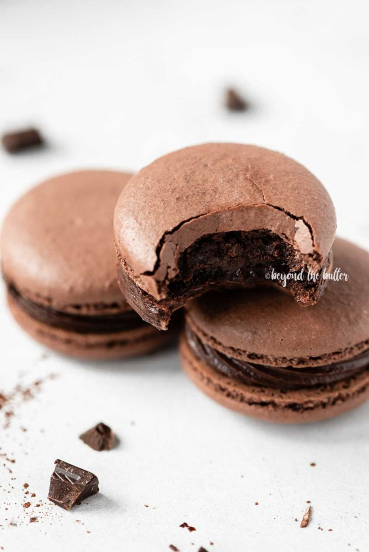 Angled image of stacked chocolate macarons with the top one having a bite taken out of it | All Images © Beyond the Butter™