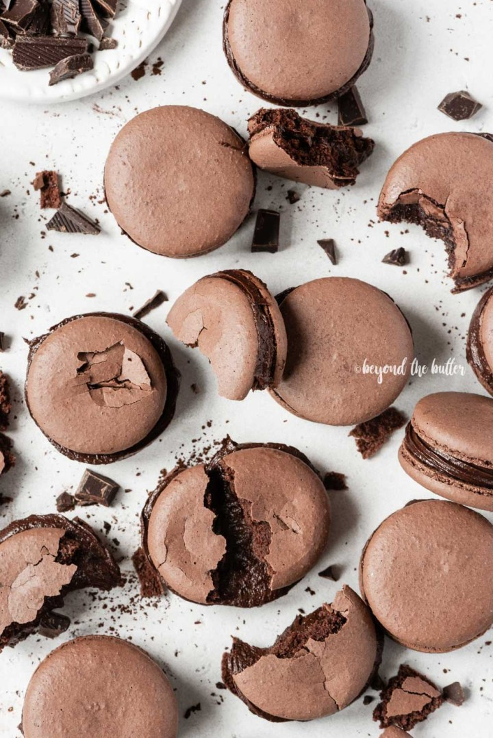 Scattered dark chocolate macarons with some broken or pulled apart   All Images © Beyond the Butter™