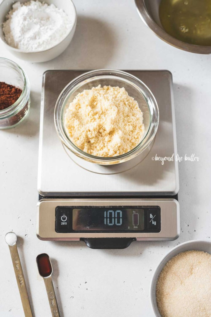 Angled image of dark chocolate macaron ingredients being weighed | All Images © Beyond the Butter™