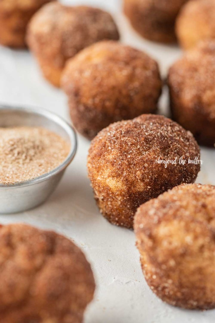 Angled image of mini french breakfast puffs on a white background with a measuring cup filled with cinnamon sugar mix   All Images © Beyond the Butter™
