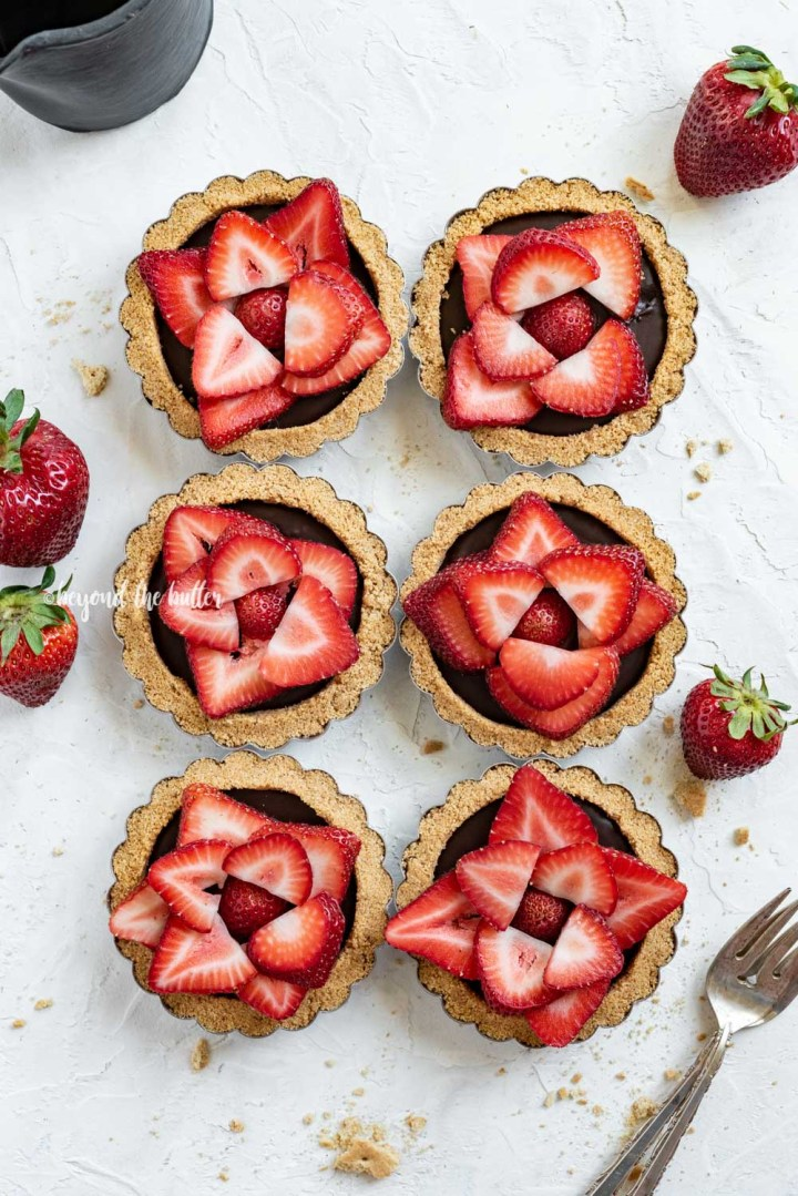 Overhead image of 6 mini strawberry nutella tarts on white stucco background with strawberries and forks around them | All Images © Beyond the Butter™