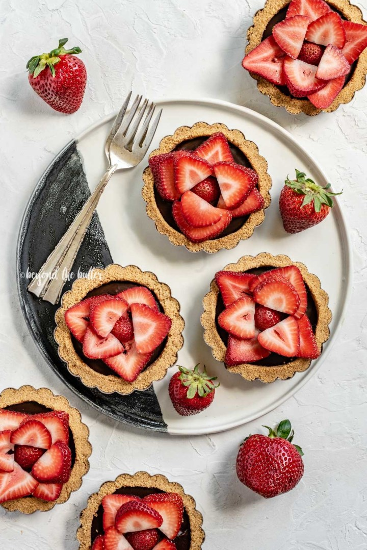 Overhead image of 6 mini strawberry nutella tarts on a black and white serving plate and randomly placed strawberries | All Images © Beyond the Butter™