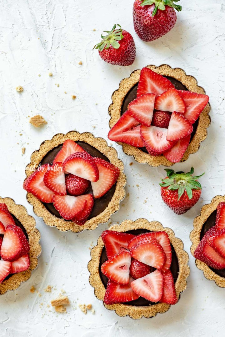 Overhead image of 6 mini strawberry nutella tarts on white stucco background with randomly placed strawberries around them | All Images © Beyond the Butter™