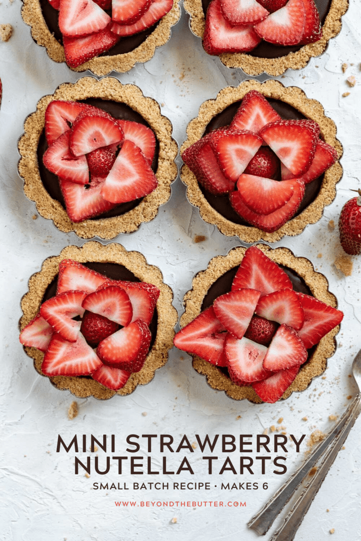 Pinterest overhead image of 6 mini strawberry nutella tarts on white stucco background with strawberries and forks around them | All Images © Beyond the Butter™