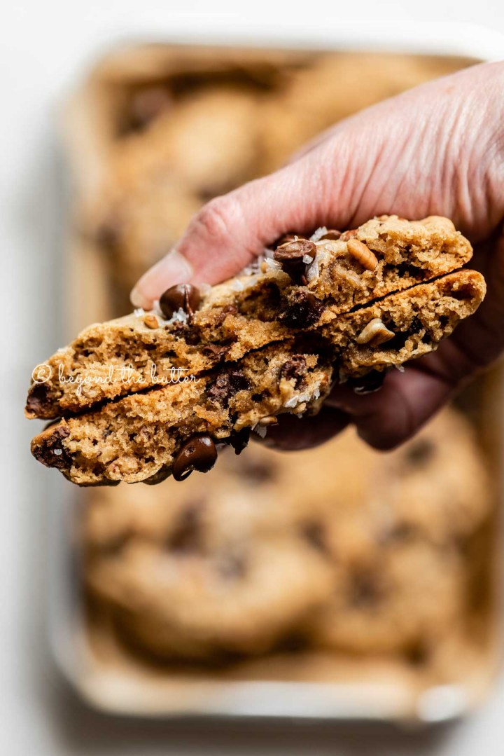 Hand holding a large almond butter chocolate chip pecan cookie that's been split in half | All images © Beyond the Butter™
